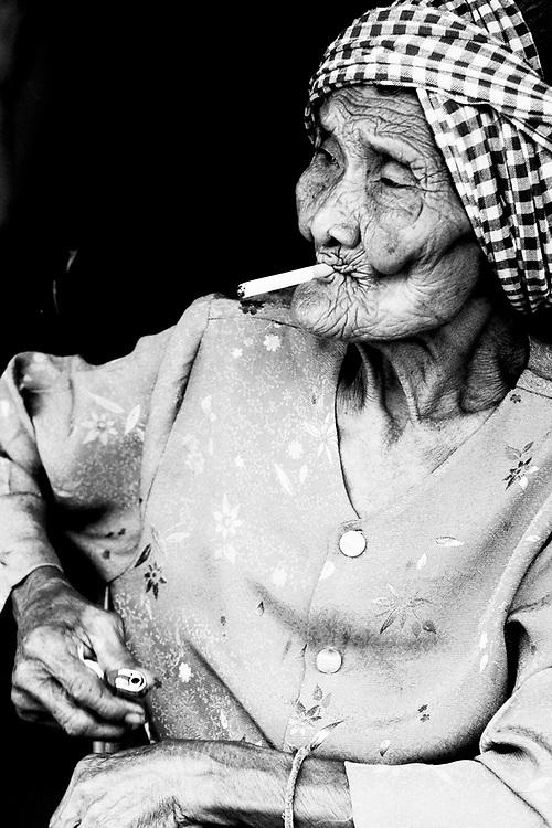 Kampot, Cambodia. Elder khmer lady smocking a cigarette. Photo by Lorenz Berna