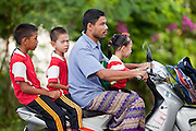 """Sept. 27, 2009 -- PATTANI, THAILAND: A man takes his children to school in Pattani, Thailand, Sept. 27.  Schools and school teachers have been frequent targets of Muslim insurgents in southern Thailand and the army now provides security at many government schools.  Thailand's three southern most provinces; Yala, Pattani and Narathiwat are often called """"restive"""" and a decades long Muslim insurgency has gained traction recently. Nearly 4,000 people have been killed since 2004. The three southern provinces are under emergency control and there are more than 60,000 Thai military, police and paramilitary militia forces trying to keep the peace battling insurgents who favor car bombs and assassination.  Photo by Jack Kurtz / ZUMA Press"""
