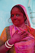Woman covered in colourful paint powder during the festival of Holi in the city of Jaipur, Rajasthan, India.