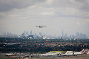 Aerial view (from control tower) of landing 747 jet and showing expanse of airport land at London Heathrow.