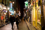 Couple stroll through Rue Gregoire de Tours past shops, near Boulevard St Germain, Left Bank, Paris, France