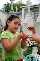 """MEXICO, Veracruz, Tantoyuca, Oct 27- Nov 4, 2009. A girl twists flowers into an offering in Tantoyuca's main cemetery. """"Xantolo,"""" the Nahuatl word for """"Santos,"""" or holy, marks a week-long period during which the whole Huasteca region of northern Veracruz state prepares for """"Dia de los Muertos,"""" the Day of the Dead. For children on the nights of October 31st and adults on November 1st, there is costumed dancing in the streets, and a carnival atmosphere, while Mexican families also honor the yearly return of the souls of their relatives at home and in the graveyards, with flower-bedecked altars and the foods their loved ones preferred in life. Photographs for HOY by Jay Dunn."""