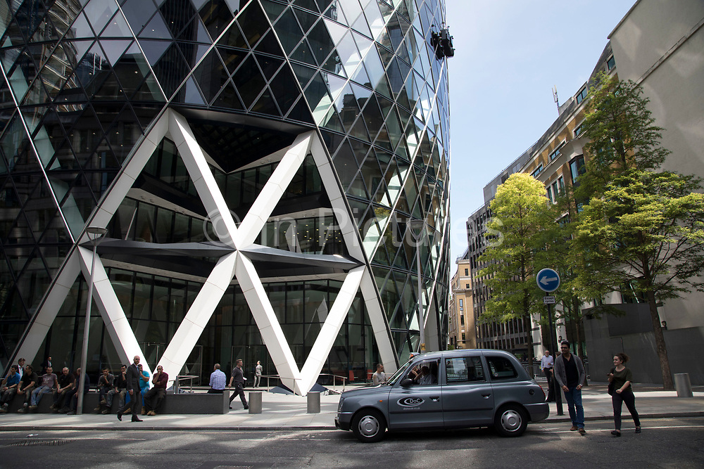 People passing by outside the Gherkin in the City of London, England, United Kingdom. Exterior of the Gherkin at 1 St Mary Axe. This iconic building is one of the best loved buildings in London with its distinctive bullet like shape and twisted glass structure.