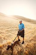 Older man walking dog in field, smiling.