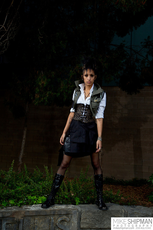 Young woman wearing steampunk fashion, corset, black skirt, military-style vest, black knee boots, posing on stone wall