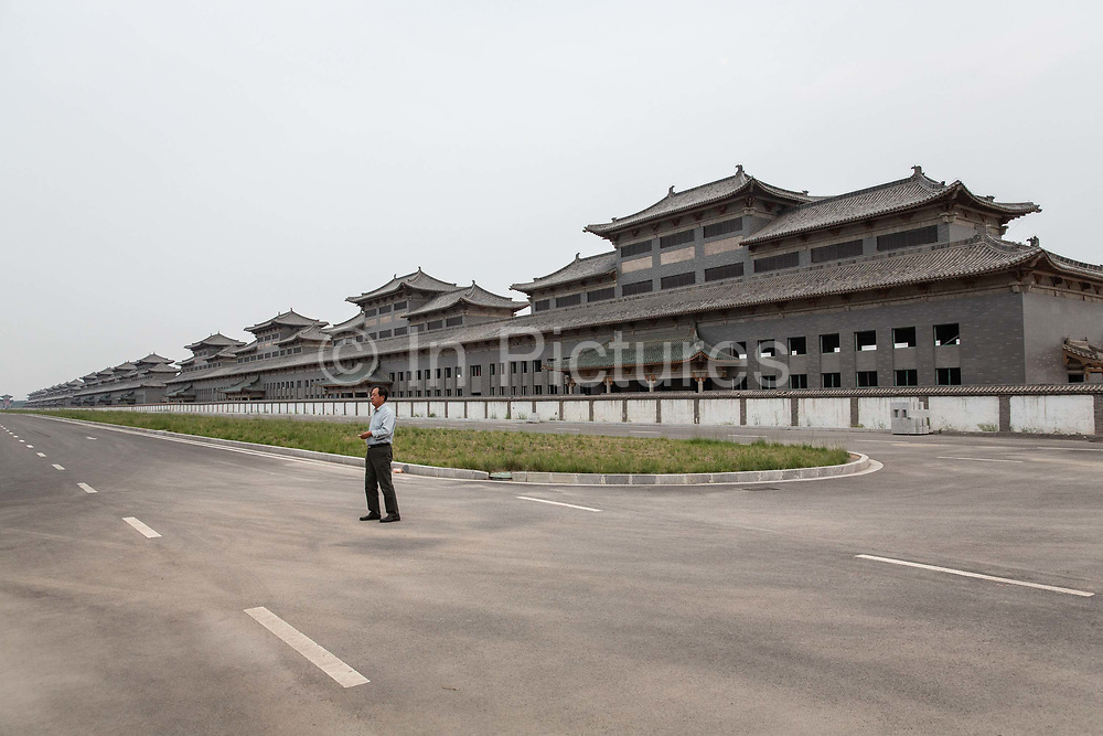 A man stands on a street with row of buildings, mostly empty, in a baijiu liquor distillery city, made in imitation of a traditional Chinese city,  in Liulin, Shanxi province, China, on Thursday, May 19, 2016. Shanxi is facing a challenge shared by a sweeping region across Chinas industrial north: how to shut down cash-burning mines that employ millions of people whose prospects are uncertain in the new economy promised by President Xi Jinping. New business ventures like the distillery city, funded by coal money with grandiose hopes and expectations, often prove too ambitious and unrealistic.