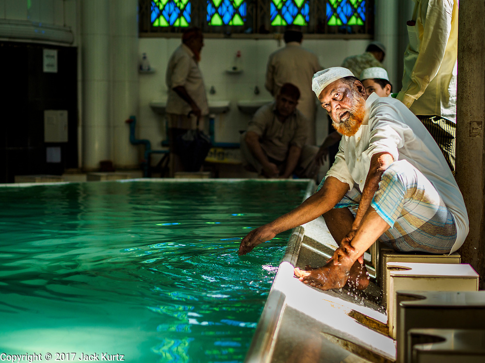 """24 NOVEMBER 2017 - YANGON, MYANMAR: A Muslim man performs ablutions before Friday prayers in Surtee Sunni Jumma Mosque in Yangon. Many Muslims in overwhelmingly Buddhist Myanmar feel their religion is threatened by a series of laws that target non-Buddhists. Under the so called """"Race and Religion Protection Laws,"""" people aren't allowed to convert from Buddhism to another religion without permission from authorities, Buddhist women aren't allowed to marry non-Buddhist men without permission from the community and polygamy is outlawed. Pope Francis is to arrive in Myanmar next week and is expected to address the persecution of the Rohingya, a Muslim ethnic minority in western Myanmar. Some Muslims and Christians are concerned that if the Pope's comments take too strong of pro-Rohingya stance, he could exacerbate religious tensions in the country.  PHOTO BY JACK KURTZ"""