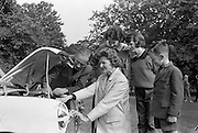 Phoenix Park Motor Race Practice.  Joe Flynn, who will compete in an A.C. Bristol in the Gold Flake Stakes in the Phoenix Park Races, gives a last minute check on his wife's car before she took off in a practice run over the course..12.07.1962