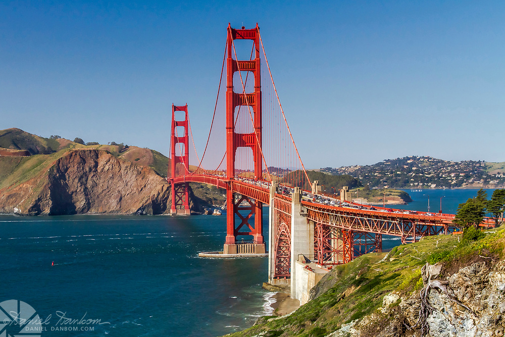 Golden Gate Bridge from the south east shoreline, with blue sky, blue water