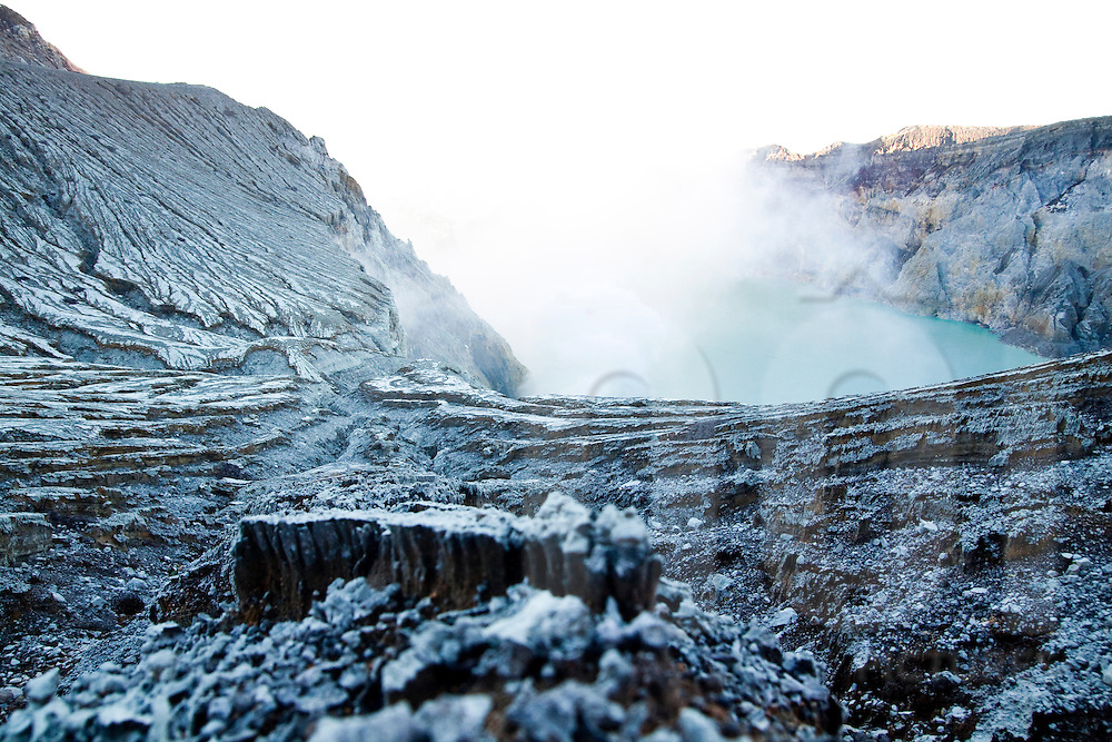 Fumes rise out of the crater lake and other-worldly landscape at the Kawah Ijen Sulphur Mines in East Java, Indonesia, Southeast Asia