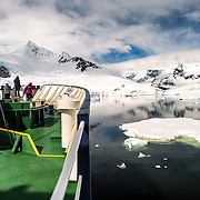An ice-strengthened ship navigating through the sea ice and still waters at Neko Harbour on the Antarctica Peninsula. The bow of the ship (Polar Pioneer) is at left, with passengers watching over the bow, with the mountains on the shore in the background.