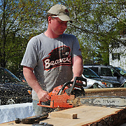 Joe begins work on a  rough cut piece of live oak to turn it into lumber that will go into the hull of the boat.