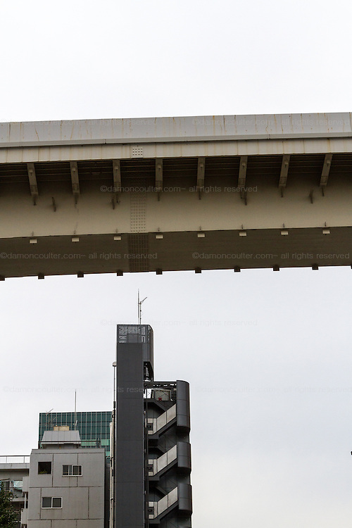 A span of one of the expressway overpasses that snake through soars above an apartment building in Tokyo, Japan. Friday September 19th 2014
