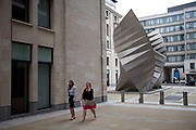 Workers walk past a large public sculpture at Paternoster Square, in the City of London.