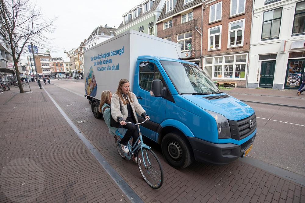 Een auto van de thuisbezorgdienst van Albert Heijn staat half op het fietspad in Utrecht en blokkeert daarmee de doorgang van fietsers.<br /> <br /> A van of Albert Heijn in blocking the bike lane in the city center of Utrecht.
