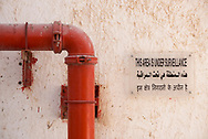 A gas or water pipeline attached to a wall next to a sign in three languages warning of surveillance in Doha, Qatar