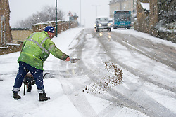 © Licensed to London News Pictures. 15/01/2013..Saltburn, Cleveland, England..As heavy snow falls on Saltburn the notorious Saltburn Bank becomes almost impassable. Here a local council worker does his best to keep traffic moving...Photo credit : Ian Forsyth/LNP