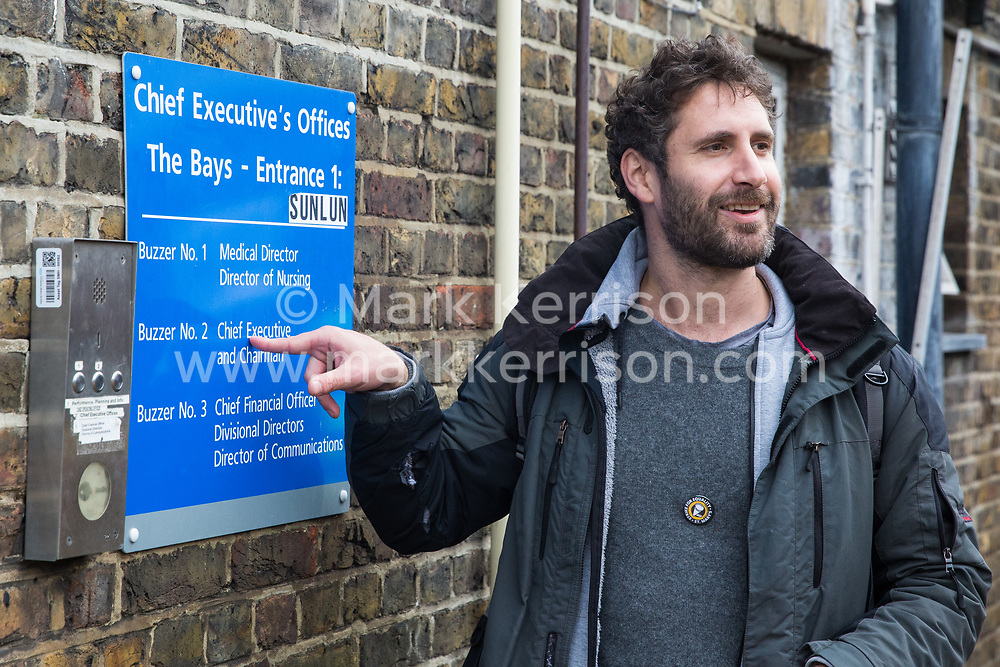 London, UK. 29 October, 2019. Petros Elia, co-founder of the United Voices of the World (UVW) trade union, indicates the office of the Chief Executive of the Imperial College Healthcare NHS Trust Professor Tim Orchard at St Mary's Hospital Paddington. UVW represents around 200 migrant cleaners, porters and caterers outsourced via Sodexo, one of the world's largest multinational corporations, who are striking for equal pay, conditions and treatment with broadly equivalent NHS colleagues who are paid £6,000-10,000 p.a. more and have scheduled 12 days of strike action.
