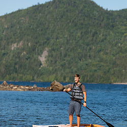 A teenage boy paddles a stand up paddle board on Deboullie Pond in Aroostook County, Maine. Deboullie Public Reserve Land.