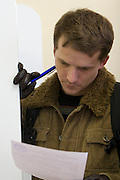 Moscow, Russia, 02/03/2008..A Russian student examines the ballot papers in the Presidential election that President Vladimir Putin's chosen heir Deputy Prime Minister Dmitry Medvedev is expected to win easily in the first round.
