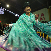 Yolanda La Amorosa dances for the audience as she is introduced before her bout during the 'Titans of the Ring' wrestling group's Sunday performance at El Alto's Multifunctional Centre. Bolivia. The wrestling group includes the fighting Cholitas, a group of Indigenous Female Lucha Libra wrestlers who fight the men as well as each other for just a few dollars appearance money. El Alto, Bolivia, 24th January 2010. Photo Tim Clayton