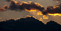 Mount Constance silouhetted against after sunset lit clouds in the Olympic Mountains of western Washington state, USA. pan