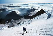 """On Mount Rainier (14,411 feet elevation or 4392 meters), a climber at 12,000 feet ascends Emmons Glacier, which terminates 7,000 feet below in the White River which flows northwest into Puget Sound. Watersheds in the upper right flow south into the Columbia River. Little Tahoma (11,138 feet) rises at right.  Permitted climbers can ascend Mount Rainier via the Camp Sherman route starting at White River Campground, in Mount Rainier National Park, Washington, USA. Published in """"Light Travel: Photography on the Go"""" book by Tom Dempsey 2009, 2010."""