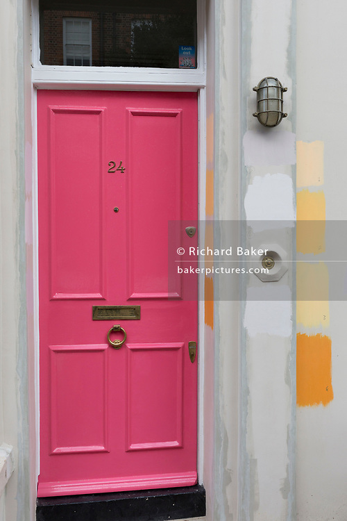 A landscape of a pink door and brass letterbox and knocker with paint swatches of orange and yellow for future masonry colour choice ideas, at a property on Portobello Road in Notting Hill, on 8th March 2020, in London, England. One neighbour of number 24 would once have been writer George Owell (while still known as Eric Blair), who lodged at number 22 in this street during the winter of 1927.