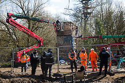 Denham, UK. 22nd March, 2021. Bailiffs from the National Eviction Team (NET) use cherry pickers during a large security operation with Thames Valley Police to dismantle a makeshift tower occupied by activists opposed to the HS2 high-speed rail link who were seeking to delay electricity pylon relocation works by Babcock in Denham Country Park.