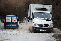 @Licensed to London News Pictures . 15/01/2015. Vans near the River Medway in Kent drive through a flooded  section of road. The River Medway between Yalding and Maidstone, including Wateringbury, West Farleigh, Teston and East Farleigh has received a flood warning following heavy rains last night and forecast again tonight (15/01/14). Photo credit: Manu Palomeque/LNP