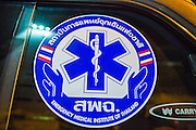 """30 NOVEMBER 2012 - BANGKOK, THAILAND: A sticker on an Ruamkatanyu Foundation ambulance. The Ruamkatanyu Foundation was started more than 60 years ago as a charitable organisation that collected the dead and transported them to the nearest facility. Crews sometimes found that the person they had been called to collect wasn't dead, and they were called upon to provide emergency medical care. That's how the foundation medical and rescue service was started. The foundation has 7,000 volunteers nationwide and along with the larger Poh Teck Tung Foundation, is one of the two largest rescue services in the country. The volunteer crews were once dubbed Bangkok's """"Body Snatchers"""" but they do much more than that now.    PHOTO BY JACK KURTZ"""