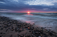 A glowing sunset kisses the waves and rocks along the Lake Superior shore.  <br /> Michigan's Upper Peninsula