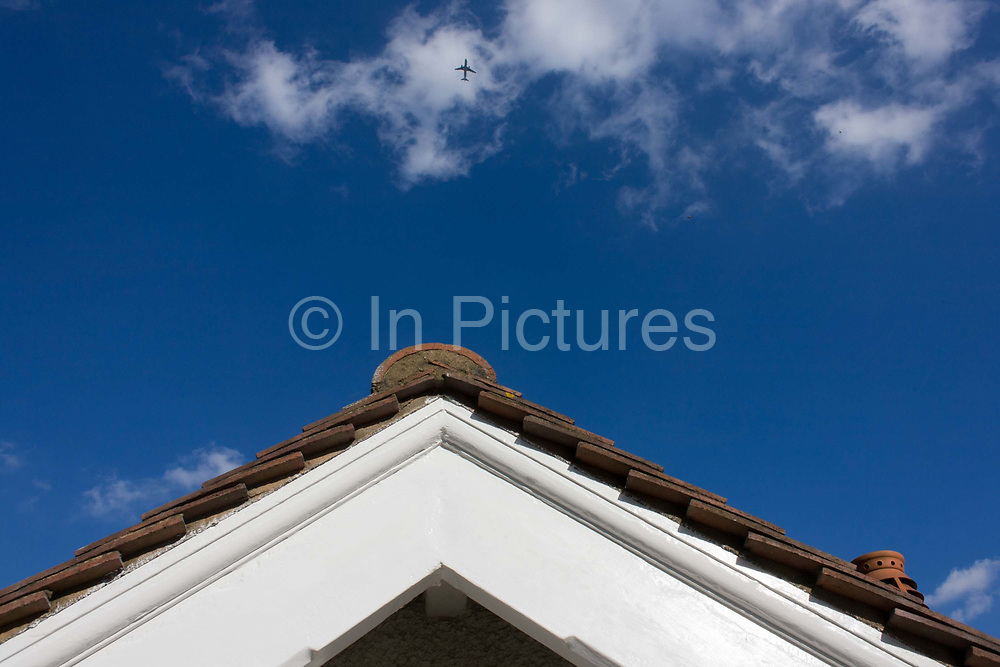 Rooftop view of a suburban Edwardian semi-detached house and overflying airliner in south London. We are high up at roof level on a sunny afternoon in the borough of Lambeth where  middle-class houses were built around the time of the first world war and whose building workforce probably did not return. The jet aircraft passes overhead, under the flightpath of air traffic descending into Heathrow airport.