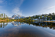 Mount Shuksan is reflected in Picture Lake after the first snowfall in Autumnl at the Mount Baker Wilderness, Whatcom County, Washington State, USA