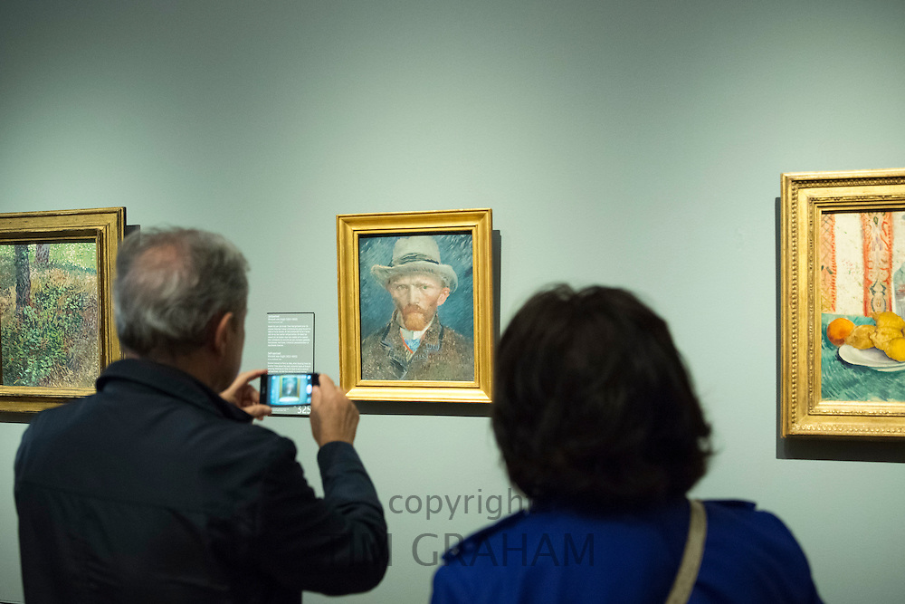 Visitor using smartphone to photograph self portrait by Vincent Van Gogh at Rijksmuseum, Amsterdam, Holland