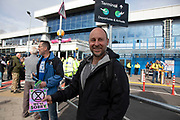 Extinction Rebellion hand out leaflets during disruption outside City Airport on 10th October 2019 in London, England, United Kingdom. The protest is against the climate and pollution impact of the government's plans for airport expansion which will potentially double the amount of flights coming from City Airport. Extinction Rebellion is a climate change group started in 2018 and has gained a huge following of people committed to peaceful protests. These protests are highlighting that the government is not doing enough to avoid catastrophic climate change and to demand the government take radical action to save the planet.