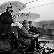 Ladies travel in style on a horse and cart while using umbrellas' to protect themselves from the rain on a country road in Maramures, Romania. Photo Tim Clayton..Romania entered the European Economic Community in January 2007, signaling a fresh exodus of the work force as many Romanians fled the country in search of a better life. Sadly many have not found the employment sought and Romanian communities camped in European cities are making headlines for all the wrong reasons...In a nation recovering from communist rule from 1947 to 1989 and a decade of economic instability and decline that followed, it is estimated Romania has lost between 2.0 and 2.5 million of it's workforce since the end of communist rule. Considering Romanian's population is estimated at 22 million, this is about 10% of the Country's population...Life goes on as normal for those who have remained in Romania. In a country steeped in history and culture there has been little or no change in age old traditions, life is personified in the rural communities where a third of Romanian's population is employed in agriculture and primary production, one of the highest in Europe.