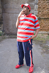 Young man standing outside a boarded up building smoking a cigarette,