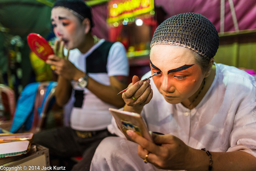 """28 JANUARY 2014 - BANGKOK, THAILAND: Performers with the Tear Kia Ee Lye Heng opera troupe put on their makeup before a show. They were performing for a business in the Min Buri district of Bangkok for the Lunar New Year, which this year is Jan 31. Chinese opera was once very popular in Thailand, where it is called """"Ngiew."""" It is usually performed in the Teochew language. Millions of Teochew speaking Chinese emigrated to Thailand (then Siam) in the 18th and 19th centuries and brought their cultural practices with them. Recently the popularity of ngiew has faded as people turn to performances of opera on DVD or movies. There are still as many 30 Chinese opera troupes left in Bangkok and its environs. They are especially busy during Chinese New Year when they travel from Chinese temple to Chinese temple performing on stages they put up in streets near the temple, sometimes sleeping on hammocks they sling under their stage. They are also frequently hired by Chinese owned businesses to perform as a form of merit making.    PHOTO BY JACK KURTZ"""