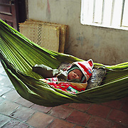 A two month old baby boy asleep in a hammock in Tang Tien, a bamboo basket weaving village, Bac Giang province, Vietnam. With Vietnam's growing population making less land available for farmers to work, families unable to sustain themselves are turning to the creation of various products in rural areas.  These 'craft' villages specialise in a single product or activity, anything from palm leaf hats to incense sticks, or from noodle making to snake-catching. Some of these 'craft' villages date back hundreds of years, whilst others are a more recent response to enable rural farmers to earn much needed extra income.