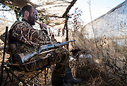 Vance Fielder blows a duck call while hunting in a duck blind on a private watershed lake in Shamrock, Oklahoma