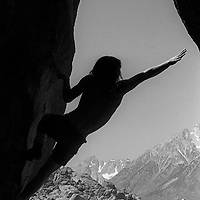 Roger Schley reaches for a key hold on a boulder problem in the Buttermilk Rocks near Bishop, California.  circa 1975