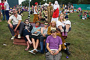 People sitting on a sofa watch a band play on the main stage at the Standon Calling Festival in Hertfordshire, UK.Standon Calling is a small independent festival set among the hills in Herfordshire that showcases World Music, Indie Music and dance Music. It is one of the new, small and quirky boutique festivals which have become popular in the UK...