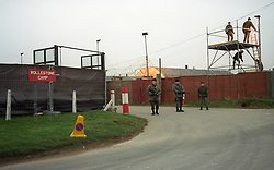 Armed soldiers of the Devonshire and Dorset Regiment stand guard on a tower and at the entrance to Rollestone Camp, Salisbury Plain, where 35 Iraqi soldiers were settling down as prisoners of war.