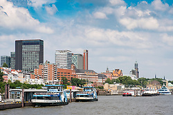 Skyline of Hamburg and ferry landing bridges from the River Elbe in Germany