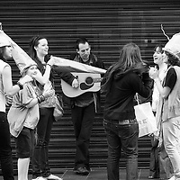 A guy on the street plays some tunes while girls in very strange looking hats stop to enjoy his music.