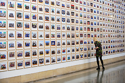 "© Licensed to London News Pictures. 11/11/2019. LONDON, UK. A staff member views works at the preview of ""Year 3"", an exhibition by Turner Prize-winning artist and Oscar-winning filmmaker Steve McQueen at Tate Britain.  The artwork comprises 3,128 traditional school class photographs of Year 3 pupils from 1,504 of London's primary schools.  The work reflects a picture of the present and is on display 12 November to 3 May 2020.  Photo credit: Stephen Chung/LNP"