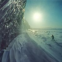 Jay Jensen skis on the frozen Arctic Ocean fjord below ice cliffs of the Nordenskjold Glacier on Spitsbergen Island, Norway.