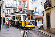 Historic famous number 28 tram carrying local people and tourists on tram tracks along shopping street in Alfama District, Lisbon, Portugal