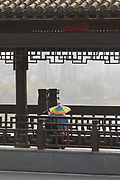Rear view of a tourist couple sitting on the wooden Wenfeng Bridge, Tunxi district, Huangshan City, Anhui Province, China